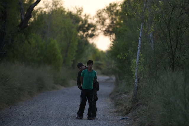 A U.S. Border Patrol agent apprehends a migrant who illegally crossed the Rio Grande and attempted to avoid capture near Mission, Texas, U.S., July 31, 2019. (Photo by Loren Elliott/Reuters)