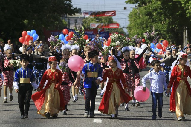 Children dressed in traditional Crimean Tatar outfits walk during a May Day rally in Simferopol, Crimea, May 1, 2016. (Photo by Pavel Rebrov/Reuters)