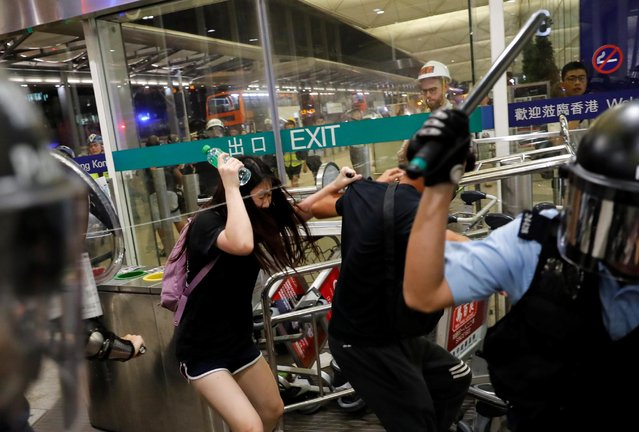 Riot police use pepper spray to disperse anti-extradition bill protesters during a mass demonstration at the Hong Kong international airport, in Hong Kong, China on August 13, 2019. Police and protesters clashed at Hong Kong's international airport on Tuesday evening after flights were disrupted for a second day and the political crisis in the former British colony deepened. (Photo by Tyrone Siu/Reuters)