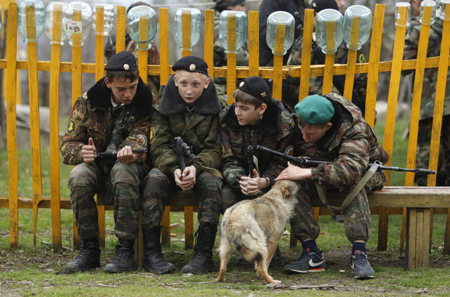 Students from the General Yermolov Cadet School sit near a dog during a two-day field exercise near the village of Sengileyevskoye, just outside the south Russian city of Stavropol, April 13, 2014. (Photo by Eduard Korniyenko/Reuters)