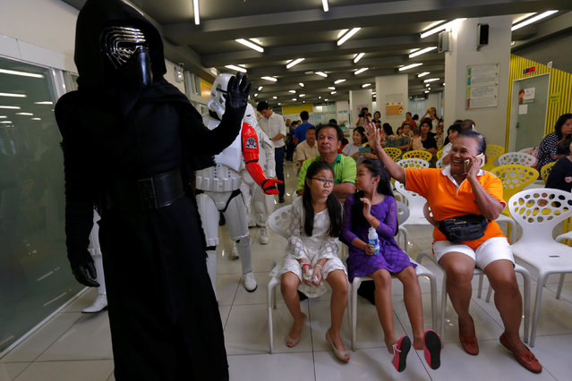 Members of a Star Wars fan club in Thailand, dressed as Kylo Ren, entertains children during Star Wars Day celebration at the Queen Sirikit National Institute of Child Health in Bangkok, Thailand, May 4, 2016. (Photo by Chaiwat Subprasom/Reuters)