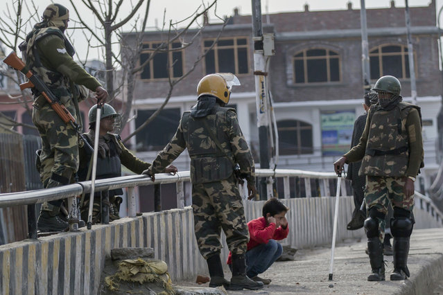 In this March 29, 2017, file photo, Indian paramilitary soldiers force a Kashmiri child to perform sit-up while holding his ear lobes, a common elementary school punishment in India, before letting him go during a strike in Srinagar, Indian-controlled Kashmir. Seeing Kashmiri residents doing calisthenics on the side of the road was once common in the 1990s, as government forces sought to humiliate people as a way of dissuading any support for armed rebels fighting against Indian rule in the disputed Himalayan territory. As the rebellion was crushed, Indian soldiers mostly stopped using public sit-ups as a form of punishment. (Photo by Dar Yasin/AP Photo)