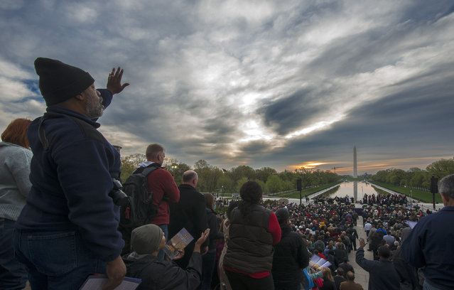 Participants sing hymns as the sun attempts to break  through clouds as the Capitol Church leads the 36th annual sunrise Easter service at the Lincoln Memorial on April, 20, 2014 in Washington, DC. (Photo by Bill O'Leary/The Washington Post)