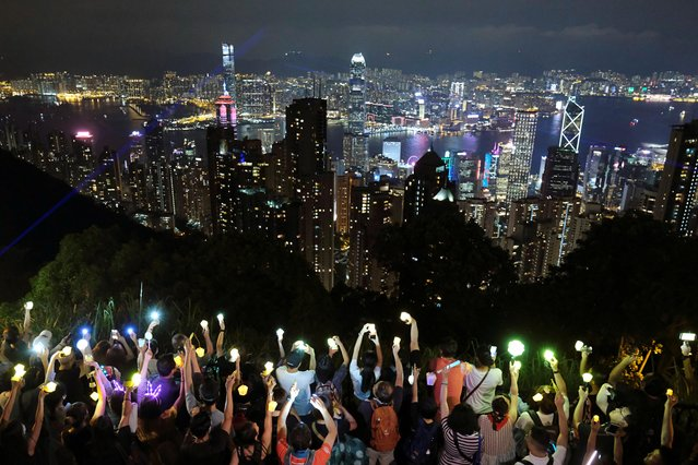 Anti-extradition bill protesters hold hands up to form a human chain during a rally to call for political reforms in Hong Kong, China on September 13, 2019. Hong Kong pro-democracy protesters took to the hills to form flashlight-carrying human chains, using the colorful Mid-Autumn Festival as a backdrop to the latest in more than three months of sometimes violent demonstrations. (Photo by Tyrone Siu/Reuters)