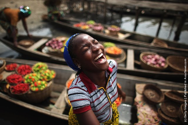 A girl laughs while unloading her boat of produce at a market in Ganvie, near Cotonou, Benin