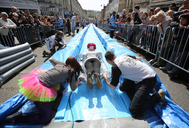 A participant on a lilo slides down a giant water slide that has been installed down Park Street on May 4, 2014 in Bristol, England. The 90m (295ft) slide was made from plastic sheets, hay bales, water and washing-up liquid and was the brainchild of artist Luke Jerram. The three hundred ticket holders who were picked from nearly 100,000 applicants took turns to hurtle down the slide watched by hundreds of spectators lining the street that was closed to traffic. (Photo by Matt Cardy/Getty Images)