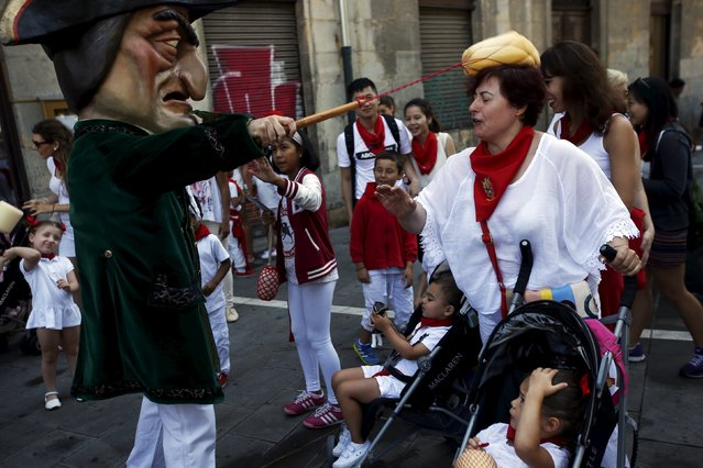 "A Kiliki hits a woman with a sponge during San Fermin festival's ""Comparsa de gigantes y cabezudos"" (Parade of the Giants and Big Heads) in Pamplona, northern Spain, July 10, 2015. (Photo by Susana Vera/Reuters)"