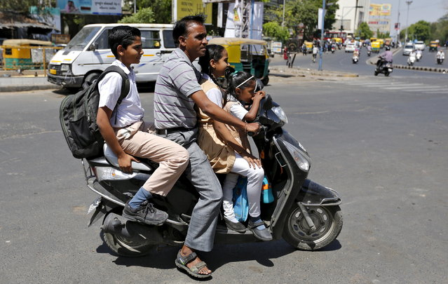 A man rides a scooter and ferries students to their school in Ahmedabad, March 22, 2016. (Photo by Amit Dave/Reuters)