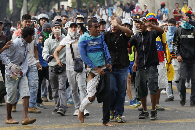 Demonstrators escort a man that was beaten, accused of been a thief, during anti-government protests in Caracas, Venezuela, Wednesday, April 19, 2017. (Photo by Ariana Cubillos/AP Photo)