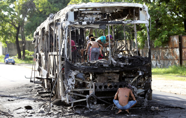People remove the remains of a burned bus in Fortaleza, Brazil, April 20, 2017. According to local media, approximately 20 buses were burned in the last two days in retaliation for the alleged transfers of prisoners held in the prisons of Fortaleza. (Photo by Paulo Whitaker/Reuters)
