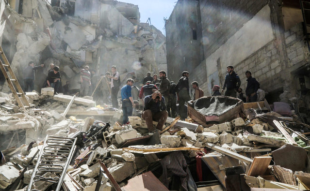 A Syrian mourns as members of the Syrian civil defence volunteers, also known as the White Helmets, and people search for survivors from the rubble following reported air- strikes on the rebel- held town of Saqba, in Eastern Ghouta, on April 4, 2017. (Photo by  Amer Almohibany/AFP Photo)