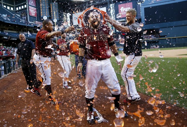 Arizona Diamondbacks' Daniel Descalso, center, celebrates his walkoff two-run home run against the Colorado Rockies with Yasmany Tomas, left, and Jeremy Hazelbaker, right, after a baseball game Sunday, April 30, 2017, in Phoenix. (Photo by Ross D. Franklin/AP Photo)