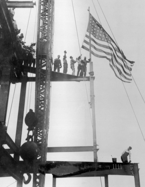 Construction workers celebrate the completion of the iron work on the Empire State Building, Manhattan, circa 1930. The building was constructed between 1930 and 1931. (Photo by FPG/Hulton Archive/Getty Images)