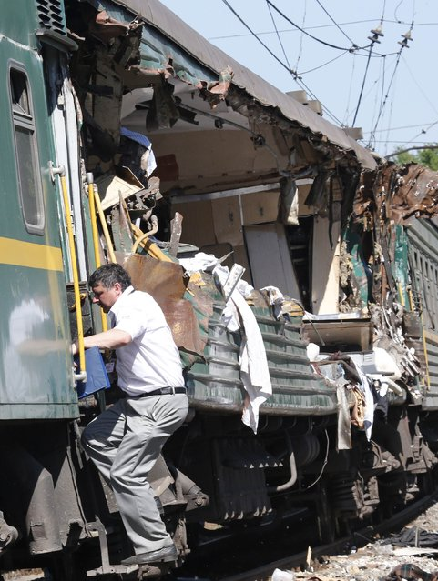 A man gets into a passenger train damaged in a collision with a freight train in Moscow region May 20, 2014. The passenger train on its way to Moldova collided with a freight train near Moscow on Tuesday, killing at least four people and injuring 15, a spokeswoman for Russia's Emergencies Ministry said. The reason for the collision, near the town of Naro-Fominsk 55 km (34 miles) southwest of Moscow, was not immediately clear. (Photo by Grigory Dukor/Reuters)