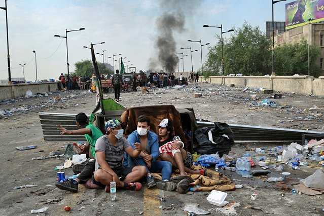 Anti-government protesters take cover while Iraqi Security forces close the bridge leading to the Green Zone, during a demonstration in Tahrir square, in Baghdad, Iraq, Sunday, October 27, 2019. (Photo by Hadi Mizban/AP Photo)