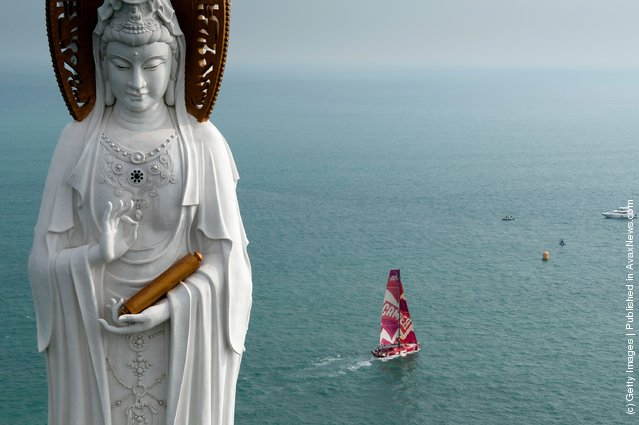 CAMPER with Emirates Team New Zealand, skippered by Chris Nicholson from Australia, sails past the Guan Yin of the South Sea of Sanya, at the start of leg 4 of the Volvo Ocean Race 2011-12