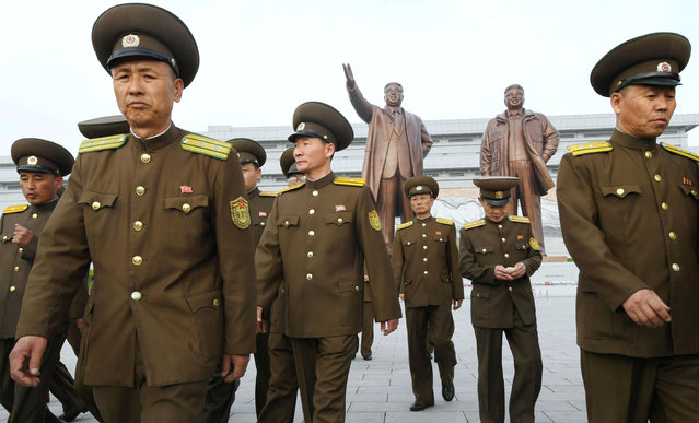 North Korean soldiers walk in front of bronze statues of North Korea's late founder Kim Il-sung and late leader Kim Jong Il at Mansudae in Pyongyang, in this photo released by Kyodo April 25, 2017, to mark the 85th anniversary of the founding of the Korean People's Army. (Photo by Reuters/Kyodo News)