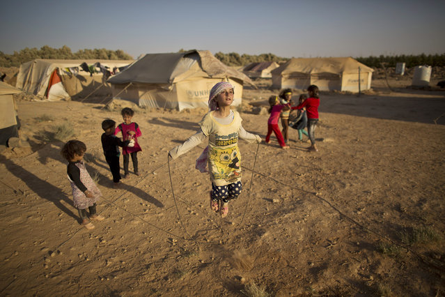 Syrian refugee girl, Zubaida Faisal, 10, skips a rope while she and other children play near their tents at an informal tented settlement near the Syrian border on the outskirts of Mafraq, Jordan, Sunday, July 19, 2015. (Photo by Muhammed Muheisen/AP Photo)