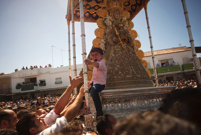 "A child cries after being placed onto the float an effigy of the virgin Mary as it is carried during a procession in the village of El Rocio, southern Spain on June 9, 2014 also home to the statue of the ""Madonna of the Dew"" that has been worshipped since 1280. El Rocio pilgrimage is the largest in Spain with hundreds of thousands of devotees wearing traditional outfits converging in a burst of colour as they make their way on horseback and decorated carriages across the Andalusian countryside. (Photo by Jorge Guerreo/AFP Photo)"