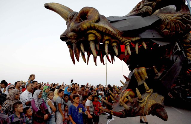 People play with a statue of a dragon during the Aoussou Carnival in Sousse, Tunisia July 26, 2015. (Photo by Anis Mili/Reuters)
