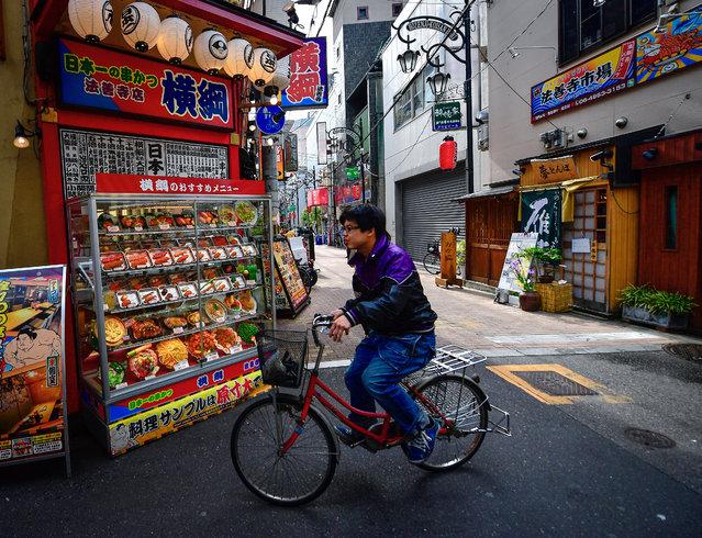 A local resident cycles past stalls in Namba district. Osaka, Japan on May 15, 2017. (Photo by Yuri Smityuk/TASS)