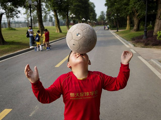 A student balances the ball on his nose as he walks to a training match at the Evergrande International Football School near Qingyuan in Guangdong Province. (Photo by Kevin Frayer/Getty Images)