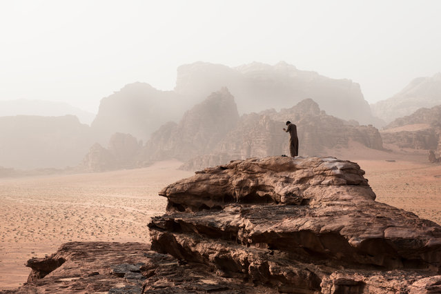 """Bedouin in Wadi Rum"". People have lived and traveled through Wadi Rum in Jordan for thousands of years and although the place has become very touristic, the locals still manage to find a peaceful moment from time to time. Photo location: Wadi Rum, Jordan. (Photo and caption by Catalin Marin/National Geographic Photo Contest)"