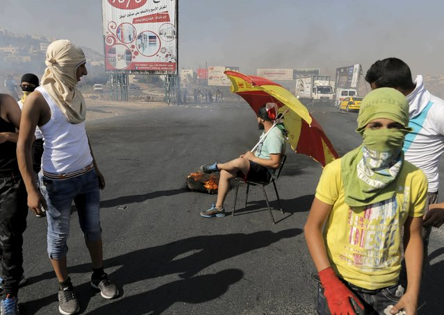 A Palestinian protester sits on the road during clashes with Israeli troops following the killing of a 18-month-old Palestinian toddler, at the Israeli Hawara checkpoint near the West Bank city of Nablus July 31, 2015. Suspected Jewish attackers torched a Palestinian home in the occupied West Bank on Friday, killing an 18-month-old toddler and seriously injuring three other family members, an act that Israel's prime minister described as terrorism. (Photo by Ammar Awad/Reuters)