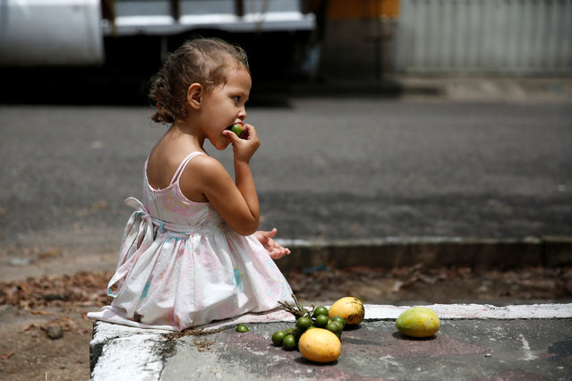 """A girl eats a tropical fruit called """"Mamon"""" while seated next to some mangoes on a street in La Fria, Venezuela, June 2, 2016. (Photo by Carlos Garcia Rawlins/Reuters)"""