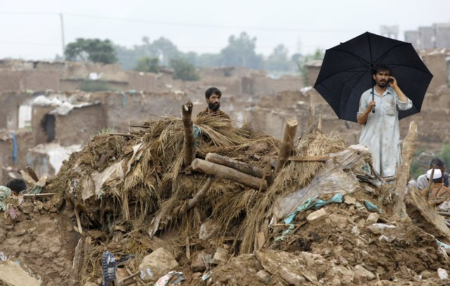 Men stand on the rubble of what used to be their home in a slum in Islamabad, Pakistan August 1, 2015. According to local media, the Capital Development Authority (CDA) has started to demolish illegal settlements on the outskirts of Islamabad where Afghan refugees and people from Pakistan's tribal area have escaped from the military operations. (Photo by Caren Firouz/Reuters)