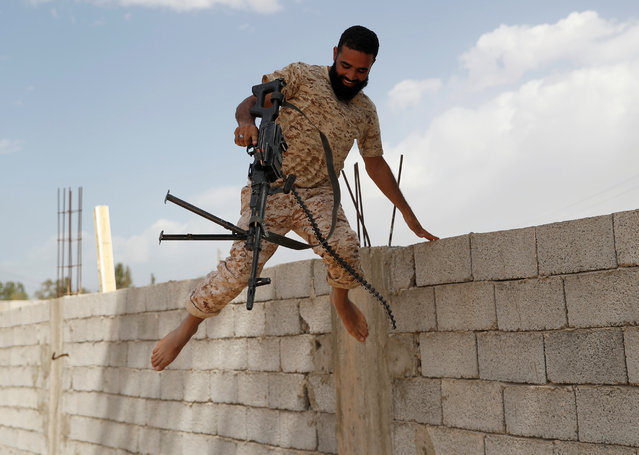 A member of the Libyan internationally recognised government forces jumps from a wall after he fired a rifle on the outskirts of Tripoli, Libya on May 12, 2019. (Photo by Goran Tomasevic/Reuters)