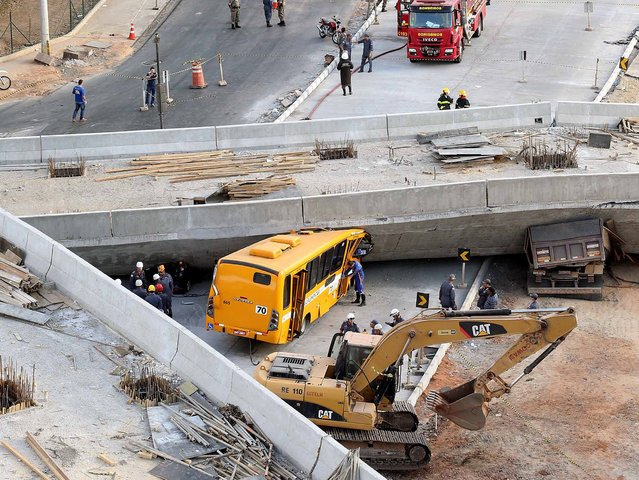 Rescue workers try to reach vehicles trapped underneath a bridge that collapsed while under construction in Belo Horizonte July 3, 2014. An unfinished overpass collapsed in the Brazilian World Cup host city of Belo Horizonte on Thursday, killing at least two people, emergency officials said. (Photo by Carlos Greco/Reuters)
