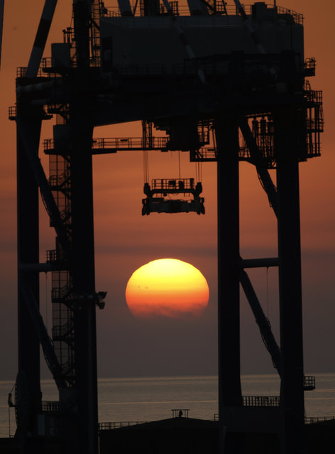 The sun sets behind a crane at the Gioia Tauro port, southern Italy, Wednesday, July 2, 2014. Cargo containers carrying hundreds of tons of Syrian chemical weapons were loaded onto a U.S. cargo ship Wednesday for destruction at sea, one of the final phases of the international effort to rid Syria of its chemical weapon stockpile.(Photo by Luca Bruno/AP Photo)