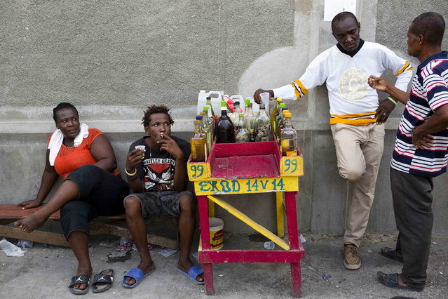 Eddy Lecty, who sells the sugar-based alcoholic drink known as clairin, second from right, talks to a client as his relative Junior Lecty and local Suzie Bazil, left, sit nearby in the Cite Soleil area of Port-au-Prince, Haiti, Tuesday, July 11, 2017. Eddy Lecty, who's selling spot has been coined by locals The Citizens Club, says people trust his product and former Haitians presidents like Rene Preval and Michel Martelly have stopped by to have a drink. (Photo by Dieu Nalio Chery/AP Photo)
