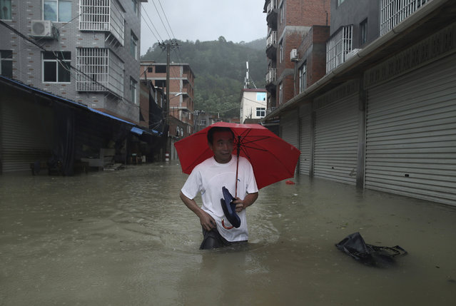 A man walks in a flooded street affected by Typhoon Soudelor in Ningde, in southeast China's Fujian province, Sunday, August 9, 2015. Typhoon Soudelor that lashed Taiwan dumped heavy rain and winds on the Chinese mainland on Sunday, leaving dozens of people dead or missing, collapsing homes and trees and cutting power to more than a million homes. (Photo by Chinatopix via AP Photo)