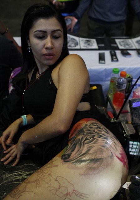 A man works on a tattoo during the 8th Expotattoo Colombia Fair in Medellin, Antioquia department, Colombia on July 14, 2017. (Photo by Joaquin Sarmiento/AFP Photo)