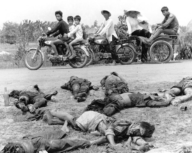 Children ride home from school past the bodies of 15 dead Viet Cong soldiers and their commander in the village of An Ninh in Vietnam's Hau Nghia province on May 8, 1972