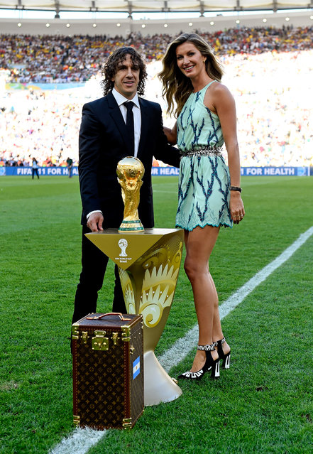 Former Spanish international Carles Puyol (L) and model Gisele Bundchen present the World Cup from a Louis Vuitton travel case prior to the 2014 FIFA World Cup Brazil Final match between Germany and Argentina at Maracana on July 13, 2014 in Rio de Janeiro, Brazil. (Photo by Mike Hewitt - FIFA/FIFA via Getty Images)