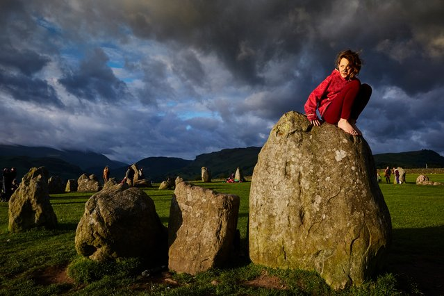 Ada Wood, 10, perches on one of Castlerigg's 38 stones during the summer solstice  at Castlerigg stone circle in Cumbria, Britain, on June 21, 2016. (Photo by Christopher Thomond/The Guardian)