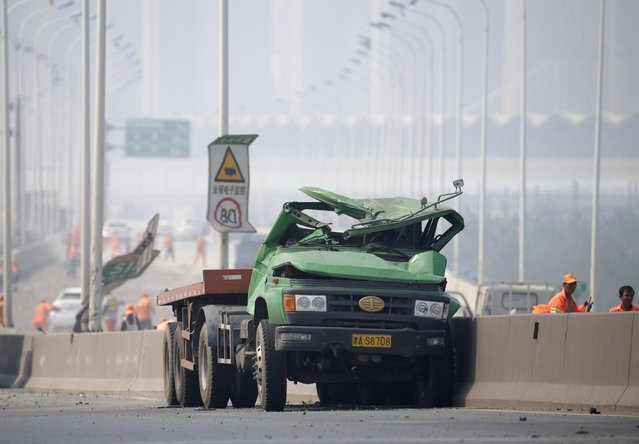 A damaged truck is seen on a highway near the site of the explosions at the Binhai new district in Tianjin August 13, 2015. (Photo by Jason Lee/Reuters)