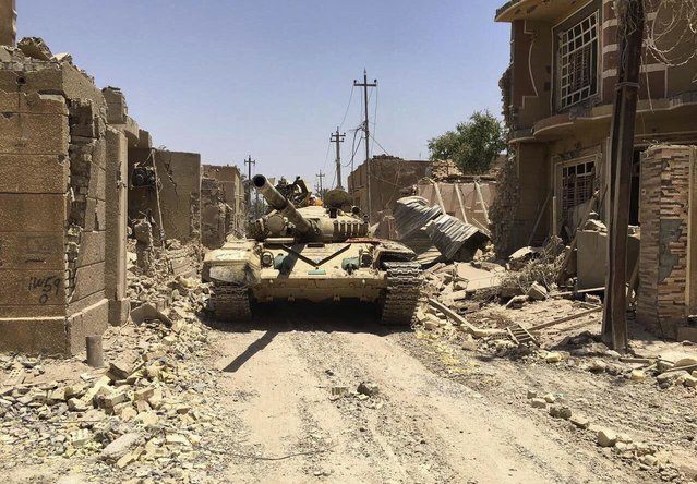 """Iraqi security forces in al-Julan neighborhood after defeating Islamic State militants in Fallujah, Iraq, Sunday, June 26, 2016. A senior Iraqi commander said the city of Fallujah was """"fully liberated"""" from Islamic State militants on Sunday, after a more than monthlong military operation. (Photo by AP Photo)"""