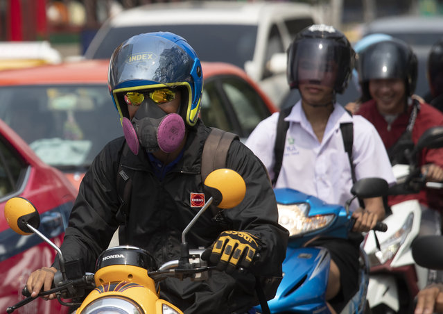 Motorcyclists wear face masks to protect from the poor air quality Bangkok, Thailand, Monday, January 20, 2020. Thick haze blanketed the Thai capital on Monday sending air pollution levels soaring to 89 micrograms per cubic meter of PM2.5 particles in some areas, according to the Pollution Control Department. (Photo by Sakchai Lalit/AP Photo)