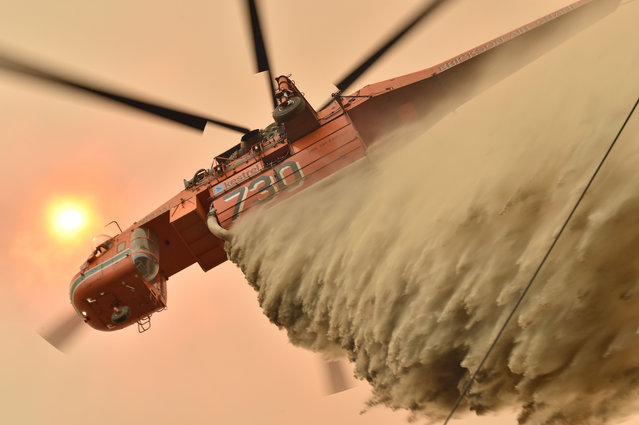 A helicopter drops fire retardent to protect a property in Balmoral, 150 kilometres southwest of Sydney on December 19, 2019. A state of emergency was declared in Australia's most populated region on December 19, as a record heat wave fanned unprecedented bushfires. (Photo by Peter Parks/AFP Photo)