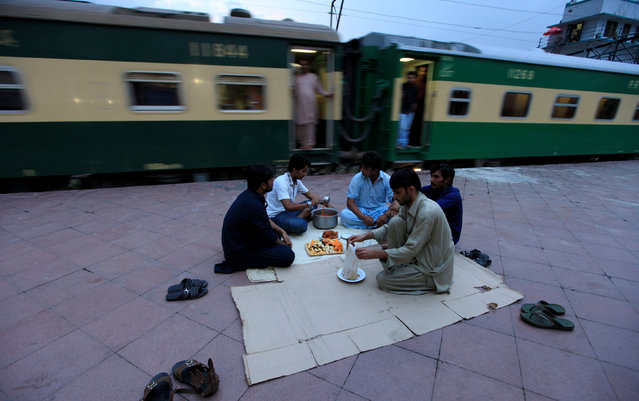 Men prepare a meal before breaking their fast during the Muslim holy month of Ramadan at a railway station in Rawalpindi, Pakistan, June 12, 2016. (Photo by Faisal Mahmood/Reuters)
