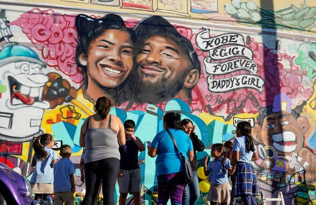 Fans gather around a mural to pay respects to Kobe Bryant after a helicopter crash killed the retired basketball star, in Los Angeles, California, U.S., January 28, 2020. (Photo by Kyle Grillot/Reuters)