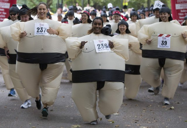 Participants take part in The Sumo Run in Battersea Park, London July 27, 2014. The runners, wearing inflatable costumes, take part in the 5km run with the aim of raising money for a charity to help educate children in Africa. (Photo by Neil Hall/Reuters)