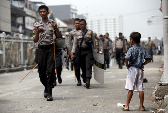 A boy watches as Indonesian police patrol a street after clashing with residents, in Jakarta's Kampung Pulo August 20, 2015. (Photo by Darren Whiteside/Reuters)