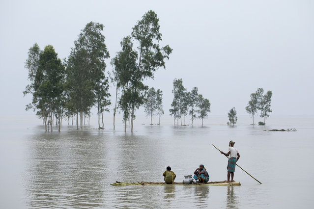"""A family travels by raft to collect drinking water near a river island formed from sedimentation, known as a """"char"""" at Mainkdir, Sariakandi, Bogra, Bangladesh, 16 August 2017. Flood victims are facing severe shortages of drinking water and food. Many flood victims have abandoned their homes along with their cattle, goats, to take shelter on embankments. At least 50 people have died as a result of the floods. (Photo by Abir Abdullah/EPA/Rex Features/Shutterstock )"""