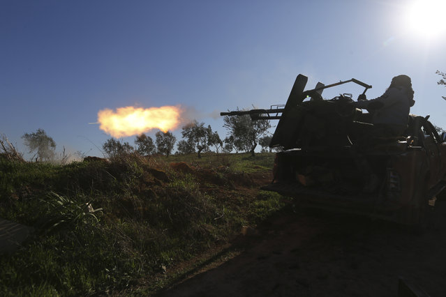 Turkish backed Syrian fighter fires at a frontline near the town of Saraqib in Idlib province, Syria, Wednesday, February 26, 2020. Syrian government forces have captured dozens of villages, including major rebel strongholds, over the past few daysin the last opposition-held area in the country's northwest. (Photo by Ghaith Alsayed/AP Photo)