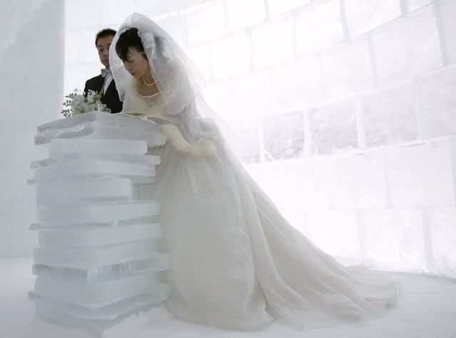 "Akemi Kito signs a covenant as her groom Hiroshi Matsuoka looks on during their wedding ceremony inside a chapel made of ice at the ""Igloo village"" on Lake Shikaribetsu in Shikaoi town in Japan's northern island of Hokkaido February 14, 2007. (Photo by Yuriko Nakao/Reuters)"